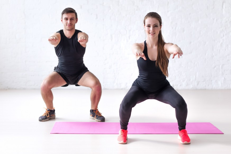 Fitness man and woman exercising squat exercise hands behind head looking at camera concept sport, training, warming up and lifestyle.